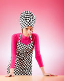 Young female cook against gradient Stock Image