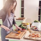 Young female cook chopping ingredients for pizza on cutting board following the recipe written in a book standing in the Stock Photo