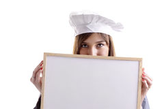 Young female cook hiding behind an ad board Royalty Free Stock Photo