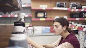 Young female costumer choosing new electric kettle in appliance store comparing different models in row on showcase. Looking for kitchenware in department of stock video footage