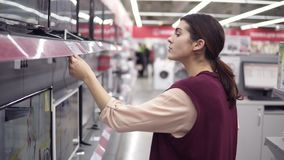Young female costumer choosing new TV set compares pricetags for different TV screens in department of electronics in. Appliance store stock footage