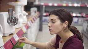 Young female costumer comparing prices for electrical meat grinders looking for perfect kitchenware in appliance store. Household equipment stock footage