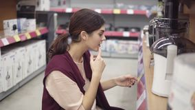 Young female costumer examining plastic containers for electrical juicer looking for perfect quality kitchenware in. Appliance store. Household equipment stock video