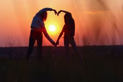 Young Female Couple Making Heart Shape With Hands At Sunset. Abstract Love Background. People, Love, Friendship Background. Female Best Friends Making A Heart royalty free stock photos