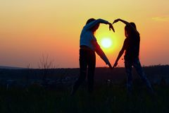 Young Female Couple Making Heart Shape With Hands At Sunset. Abstract Love Background. People, Love, Friendship Background. Female Best Friends Making A Heart royalty free stock image