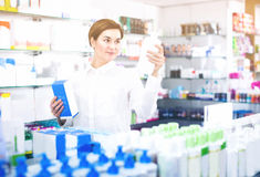 Young female customer is browsing rows of body care products. In pharmacy Stock Image