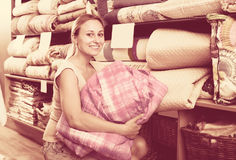 Young female customer choosing blanket. In bedding section in shop Stock Photography