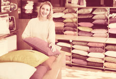 Young female customer is choosing new pillow Royalty Free Stock Images