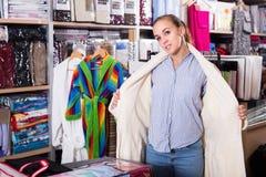 Young female customer examining new bathrobe Royalty Free Stock Images