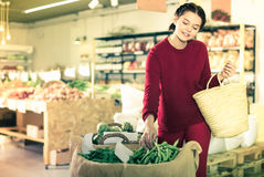 Young female customer looking green beans Royalty Free Stock Photo