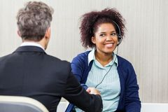 Young Female Customer Service Agent Shaking Hands Royalty Free Stock Photography