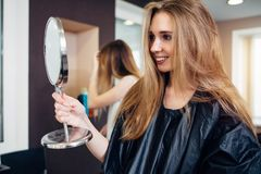 Young female customer wearing cape holding a makeup mirror looking and smiling in beauty salon satisfied with make-up stock photography