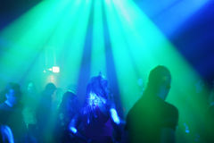 Young female dancer in/between beams of light. Dancing people in an underground club stock photo