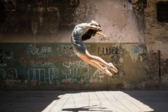 Young female dancer jumping. Dramatic portrait of a pretty female ballet dancer jumping and performing outdoors in an urban setting Stock Images