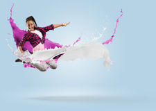 Young female dancer jumping with splash of paint Royalty Free Stock Images