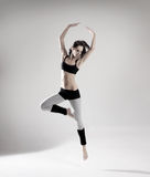 A young female dancer jumping in sporty clothes Stock Photography