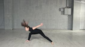 Young female dancer performing modern dance. Beautiful young dancer in black suit dancing contemporary dance on studio background stock footage