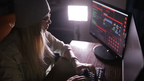 Young female in dark inputting data, computer codes, breaking security system. stock video