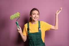 Young female decorator with paint roller. Near color wall royalty free stock photo