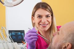 Female dentist examining patient. Young female dentist examining mature male patient with periodontal probe Royalty Free Stock Photo