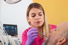 Female dentist examining patient Royalty Free Stock Photography