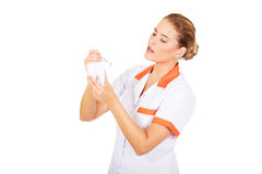 Young female dentist holding a tooth model and dental mirror Stock Photo