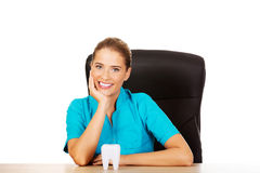 Young female dentist holding tooth model and sitting behind the desk Stock Photography