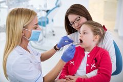 Young female dentist looks at girls teeth stock image