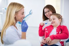 Young female dentist showing how to wash teeth stock photos