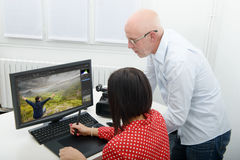 Young female designer and her boss using graphics tablet Royalty Free Stock Image