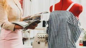 Designer with fashion magazine. Young female designer reading modern fashion magazine royalty free stock image