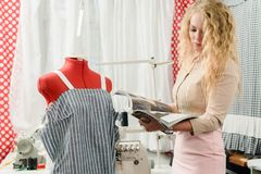 Designer with fashion magazine. Young female designer reading modern fashion magazine stock photography