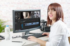 Young female designer using computer for video editing. Young smiling woman designer using computer for video editing royalty free stock photos