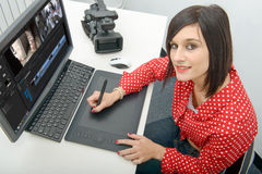 Young female designer using graphics tablet for video editing. Young brunette female designer using graphics tablet for video editing stock photography