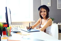 Young female designer using graphics tablet while working Royalty Free Stock Image