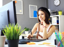 Young female designer using graphics tablet while working Royalty Free Stock Photography