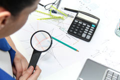 Young female designer working with architectural plan Stock Image