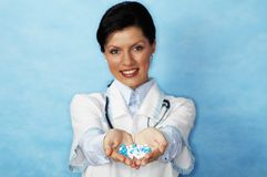 Young female doctor. Beautiful caucasian doctor with white/blue pills Royalty Free Stock Photo