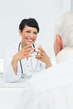 Young female doctor attentively listening to senior patient Royalty Free Stock Image