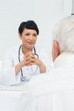 Young female doctor attentively listening to senior patient Stock Image