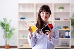The young female doctor with bag of blood plasma in hospital. Young female doctor with bag of blood plasma in hospital stock photography