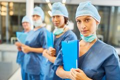 Young female doctor in blue surgical clothing with her team stock image