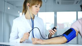 Young Female Doctor Checking Blood Pressure of Patient in Clinic. 4k , high quality Stock Photos