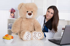 Young female doctor for children with a teddy bear. Stock Photos