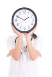 Young female doctor with clock covering face Stock Photography