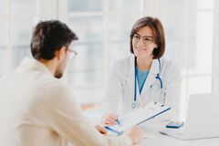 Free Young Female Doctor Consults Patient, Shows Information And Prescription In Clipboard, Talk About Medical Checkup, Pose At Clinic Royalty Free Stock Photo - 169699855