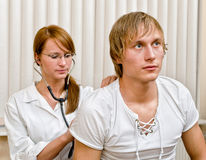 Young female doctor examine male patient Stock Photos