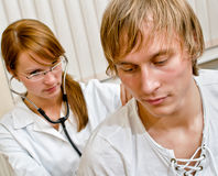 Young female doctor examine male patient Royalty Free Stock Photo