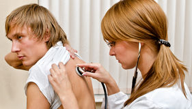 Young female doctor examine male patient Stock Image