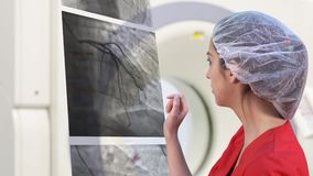Young Female Doctor Examining Cardiac X-ray. On a Virtual Screen stock video footage